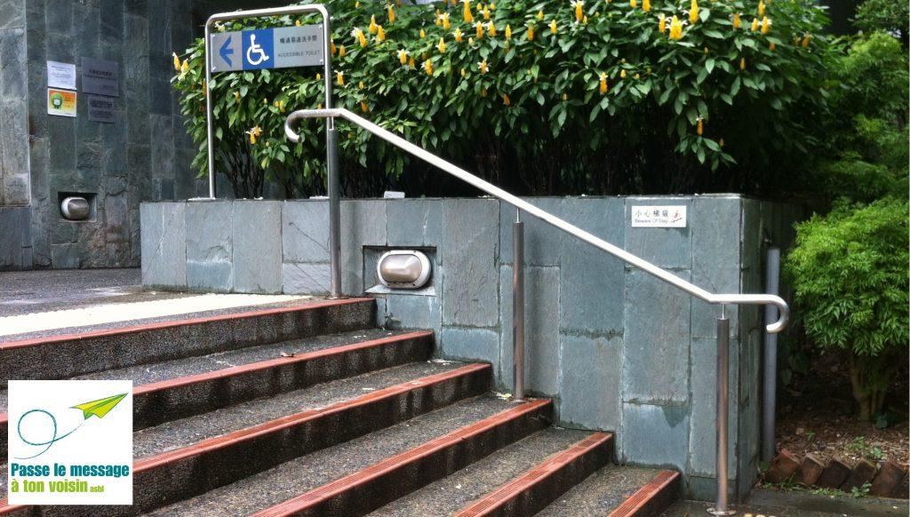 signalétique pour l'accessibilité des PMR devant un escalier