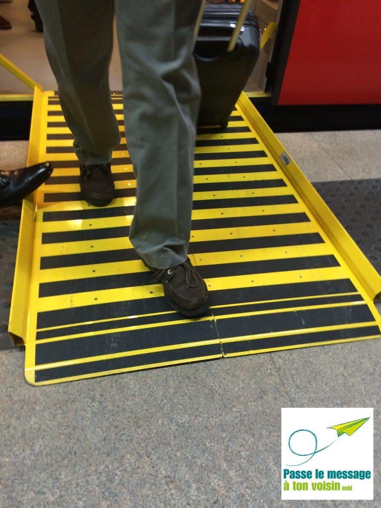 personne avec valise descendant d'un train de la SNCB, via une rampe d'accès pour améliorer l'accessibilité pour les PMR