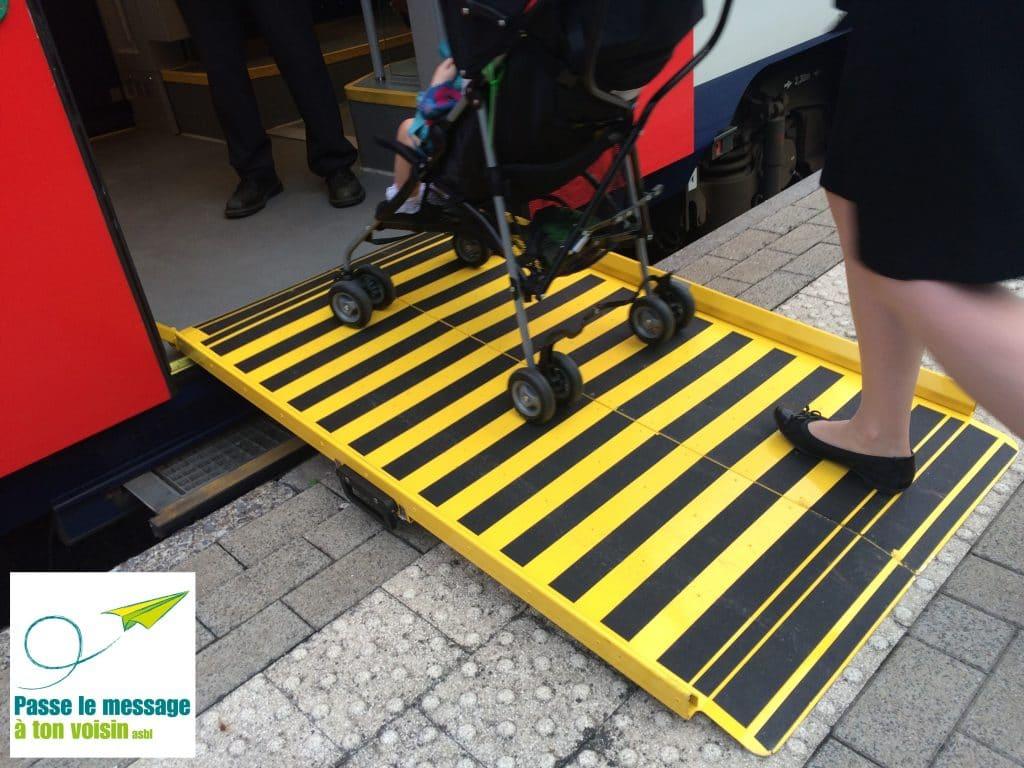 personne avec poussette montant dans un train de la SNCB, via une rampe d'accès pour améliorer l'accessibilité pour les PMR