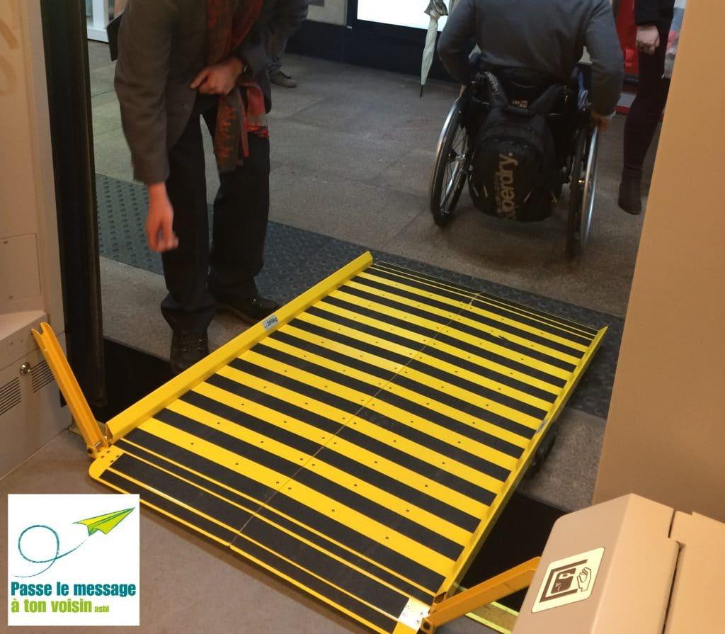 personne en chaise roulante descendant d'un train de la SNCB, via une rampe d'accès pour améliorer l'accessibilité pour les PMR
