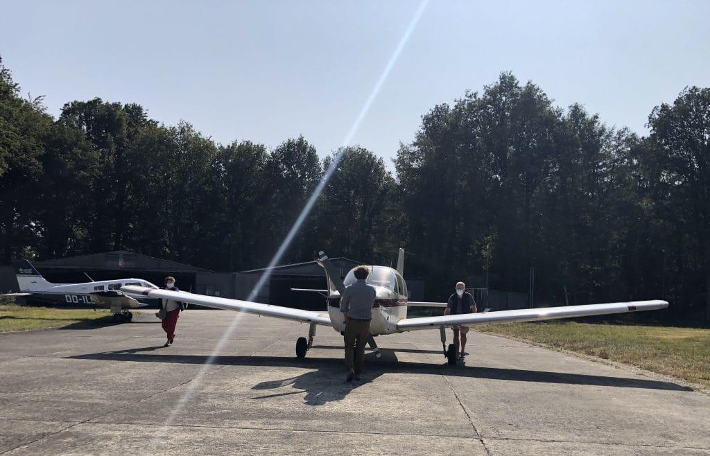 les accompagnateurs sortent l'avion du hangar